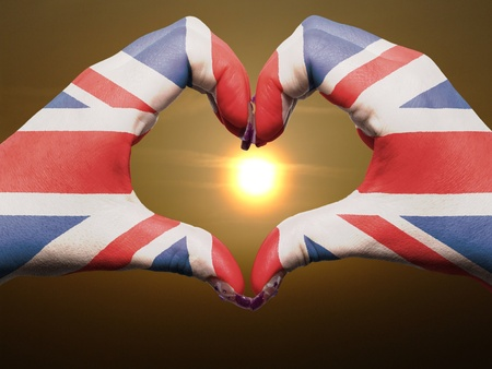Gesture made by great britain flag colored hands showing symbol of heart and love during sunrise photo