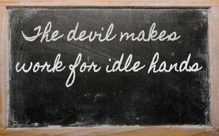 holgaz�n: escritos de escritura a mano pizarra - El diablo hace que el trabajo para las manos ociosas Foto de archivo