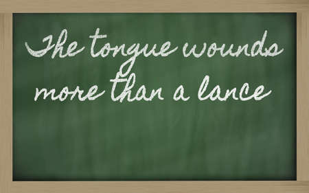 than: handwriting blackboard writings - The tongue wounds more than a lance Stock Photo