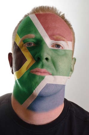 High key portrait of a serious man whose face is painted in national colors of south africa photo