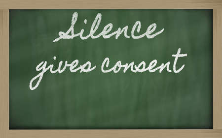 consent: handwriting blackboard writings - Silence gives consent Stock Photo