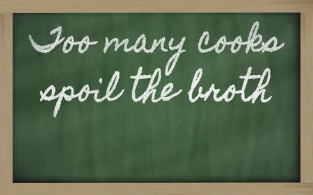 handschrift blackboard geschriften - te veel koks bederven de brij Stockfoto