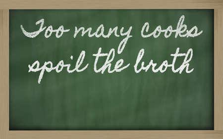 handwriting blackboard writings - too many cooks spoil the broth Фото со стока