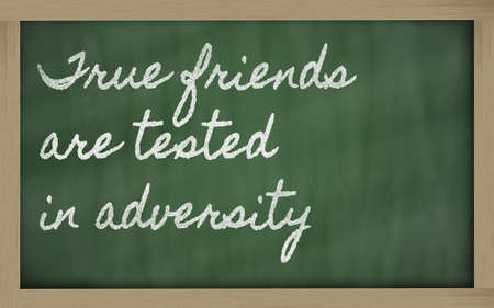 adversity: handwriting blackboard writings - True friends are tested in adversity Stock Photo