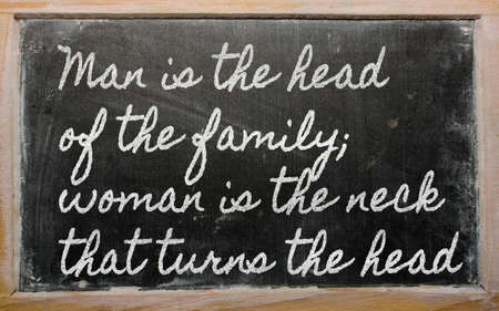 handwriting blackboard writings - Man is the head of the family;  woman is the neck that turns the head Stock Photo
