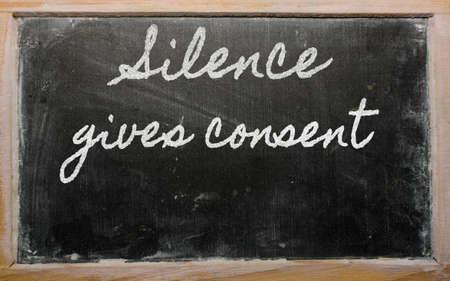 handwriting blackboard writings - Silence gives consent Фото со стока