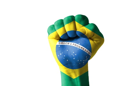 Low key picture of a fist painted in colors of brazil flag Фото со стока