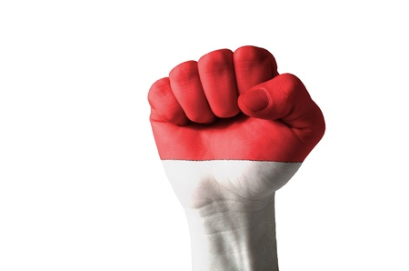 nationalism: Low key picture of a fist painted in colors of indonesia flag Stock Photo
