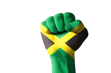 Low key picture of a fist painted in colors of jamaica flag photo