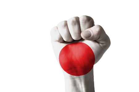 Low key picture of a fist painted in colors of japan flag photo