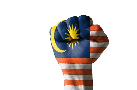 Low key picture of a fist painted in colors of malaysia flag Stock Photo