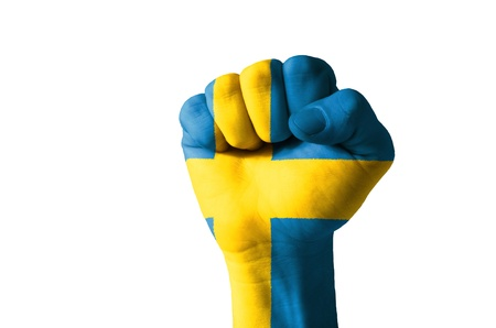 Low key picture of a fist painted in colors of sweden flag photo