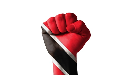 Low key picture of a fist painted in colors of trinidad tobago flag Stock Photo - 12982035