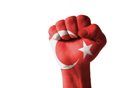 Low key picture of a fist painted in colors of turkey flag photo