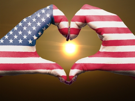 Tourist gesture made by america flag colored hands showing symbol of heart and love during sunrise