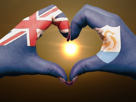 Tourist gesture made by anguilla flag colored hands showing symbol of heart and love during sunrise Stock Photo - 12981543