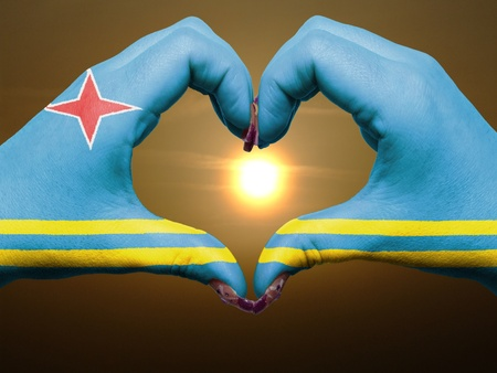 aruba flag: Gesture made by aruba flag colored hands showing symbol of heart and love during sunrise