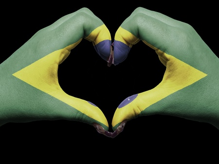 Gesture made by brazil flag colored hands showing symbol of heart and love photo