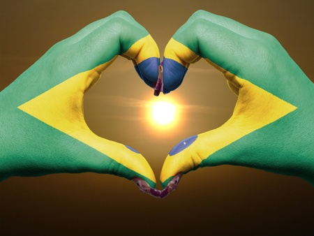 Gesture made by brazil flag colored hands showing symbol of heart and love during sunrise