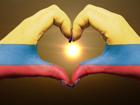 la bandera de colombia: Gesto de las manos la bandera colombia colores que muestran el s�mbolo del coraz�n y el amor durante el amanecer