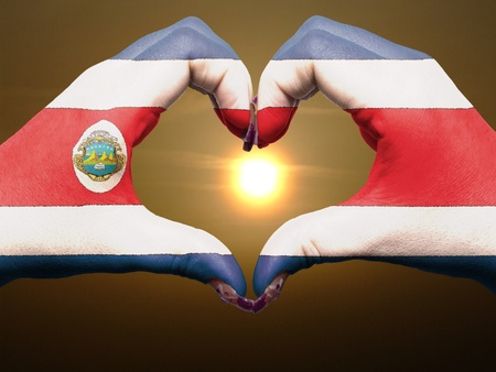 rican: Gesture made by costa rica flag colored hands showing symbol of heart and love during sunrise