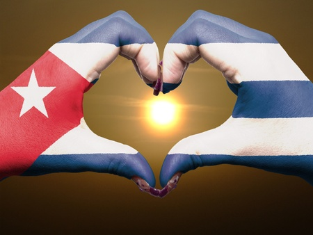 Gesture made by cuba flag colored hands showing symbol of heart and love during sunrise photo
