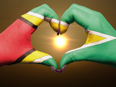 Gesture made by guyana flag colored hands showing symbol of heart and love during sunrise photo