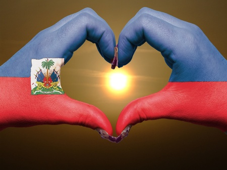 haitian: Gesture made by haiti flag colored hands showing symbol of heart and love during sunrise Stock Photo