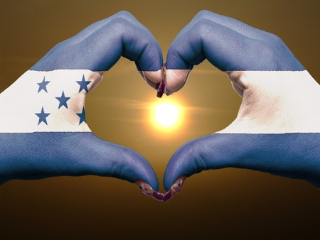 honduras: Tourist peru made by honduras flag colored hands showing symbol of heart and love during sunrise Stock Photo