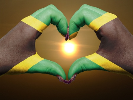 Tourist peru made by jamaica flag colored hands showing symbol of heart and love during sunrise