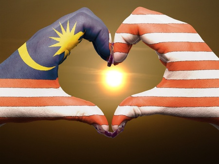 Tourist made gesture  by malaysia flag colored hands showing symbol of heart and love during sunrise photo