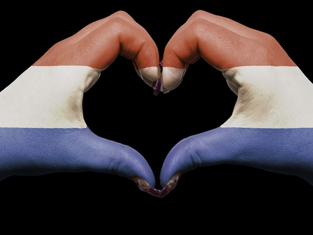 made in netherlands: Gesture made by netherlands flag colored hands showing symbol of heart and love