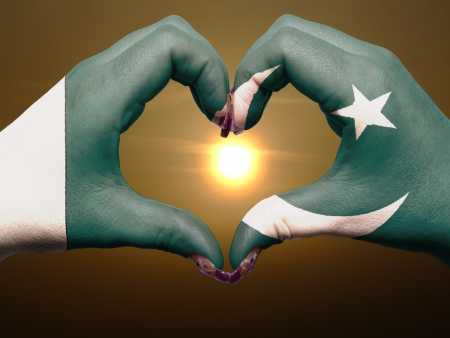 pakistani: Tourist made gesture  by pakistan flag colored hands showing symbol of heart and love during sunrise Stock Photo