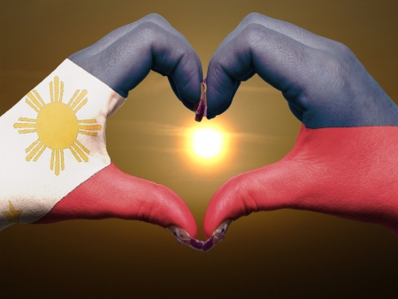 philippines: Tourist made gesture  by philippines flag colored hands showing symbol of heart and love during sunrise