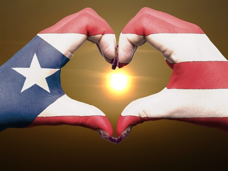 puerto rican flag: Tourist trinidad tobago made by puerto rico flag colored hands showing symbol of heart and love during sunrise