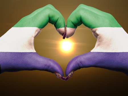 sierra: Gesture made by somalia flag colored hands showing symbol of heart and love during sunrise