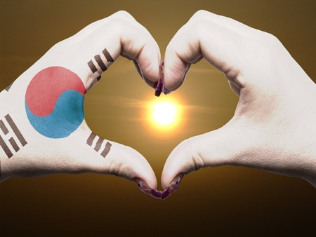 Tourist made gesture  by south korea flag colored hands showing symbol of heart and love during sunrise photo