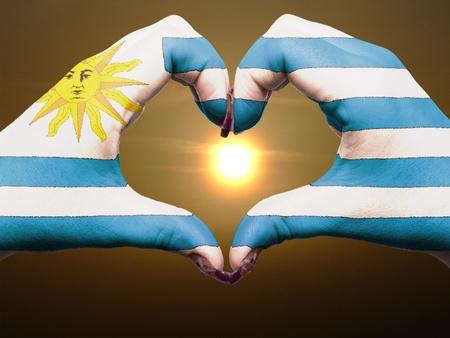 bandera de uruguay: Turismo de Uruguay hizo por Am�rica manos la bandera de colores que muestran el s�mbolo del coraz�n y el amor durante el amanecer