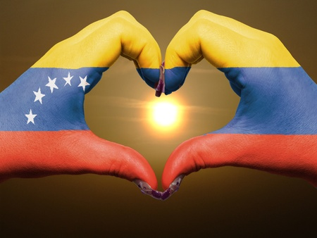 Tourist gesture made by venezuela flag colored hands showing symbol of heart and love during sunrise