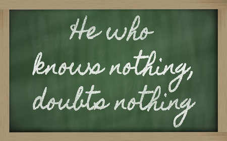knows: handwriting blackboard writings - He who knows nothing, doubts nothing Stock Photo