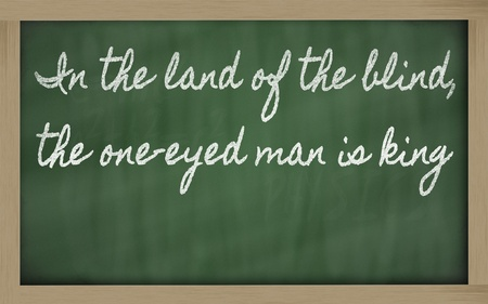 handwriting blackboard writings - In the land of the blind, the one-eyed man is king photo