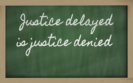 the delayed: handwriting blackboard writings - Justice delayed is justice denied Stock Photo
