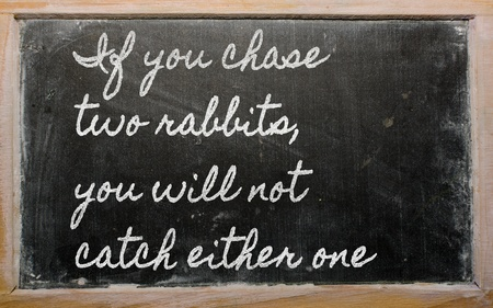 either: handwriting blackboard writings -  If you chase two rabbits, you will not catch either  one Stock Photo