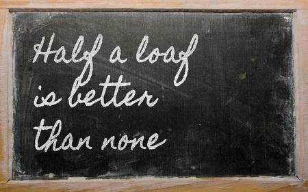 handwriting blackboard writings - Half a loaf is better than none Фото со стока