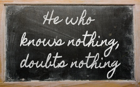 he: handwriting blackboard writings - He who knows nothing, doubts nothing Stock Photo