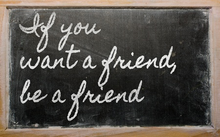 want: handwriting blackboard writings - If you want a friend, be a friend Stock Photo