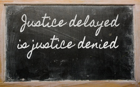 delayed: handwriting blackboard writings - Justice delayed is justice denied Stock Photo