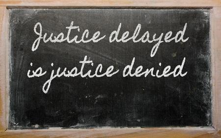 handwriting blackboard writings - Justice delayed is justice denied Фото со стока