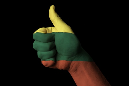 Hand with thumb up gesture in colored lithuania national flag as symbol of excellence, achievement, good, - useful for tourism and touristic advertising and also current positive political, cultural, social management of state or country Stock Photo - 12980544
