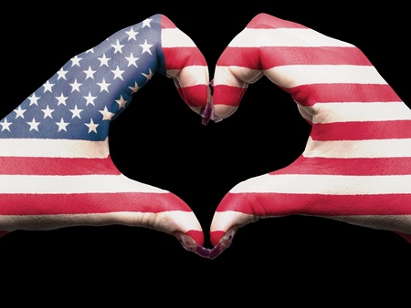 Tourist gesture made by america flag colored hands showing symbol of heart and love photo